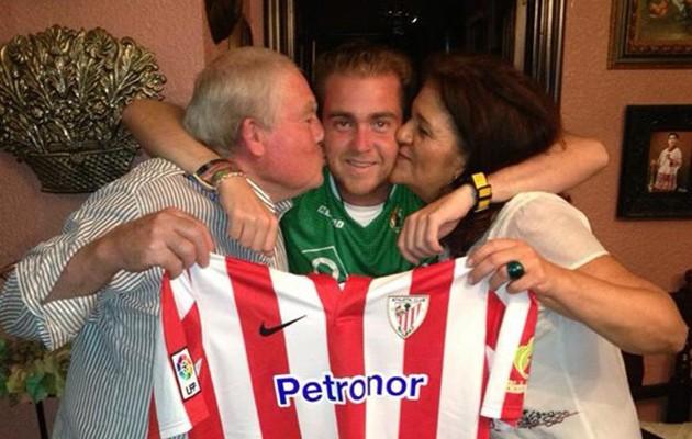 Carlos posa con sus padres y con la última camiseta que estos le han regalado