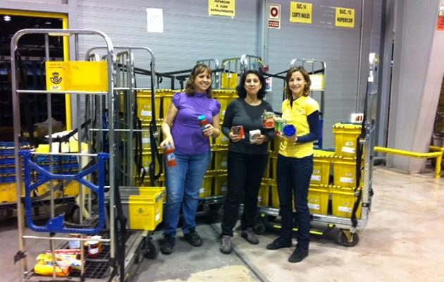 Voluntarios de Correos en el Centro de Tratamiento de Sevilla clasificando alimentos / Correos