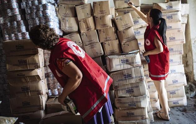 Voluntarias de Cruz Roja Internacional revisan cajas de ayuda humanitaria / EFE