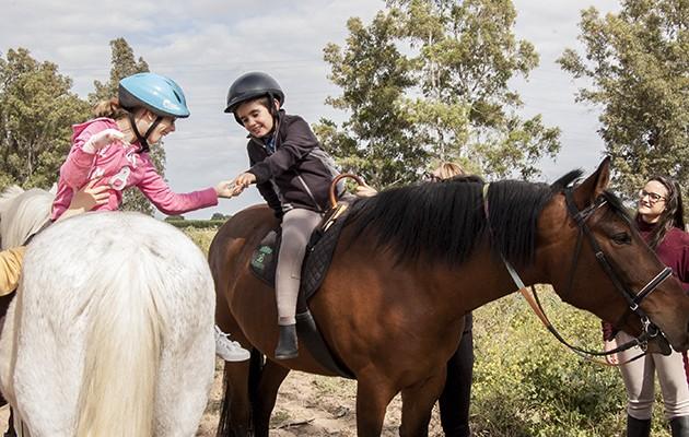 Alba y Fernando juegan encima de sus caballos como parte de la terapia