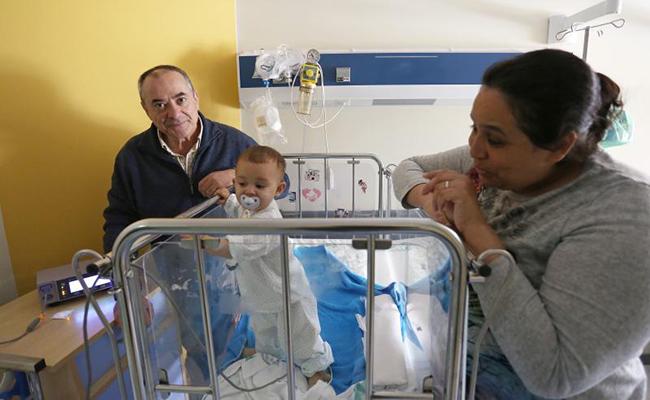 Eduardo Morales junto a Fadwa y su hijo Ayman, en el Hospital Infantil Virgen del Rocío. FOTO: VANESSA GOMEZ.