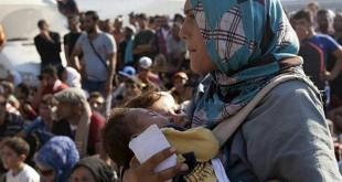 Una mujer refugiada junto a dos bebés en la isla de Lesbos, Grecia - Reuters