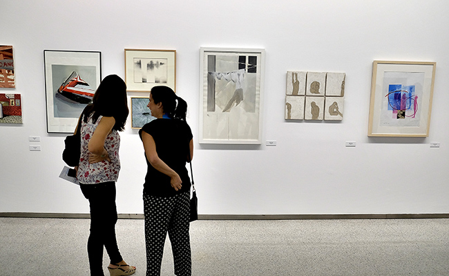 Dos jóvenes miran algunos de los cuadros de la exposición en la sala Atín Aya / J.M. SERRANO