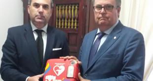 El responsable de Espacios Cardioprotegidos de la Fundación SSG, Ángel Ruiz, entrega un DEA al hermano mayor del Calvario, Francisco Javier Muela