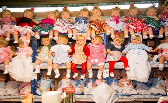 Muñecas, vestidas de flamenca, de bebé o de niña, se exponen en la estantería de la tómbola