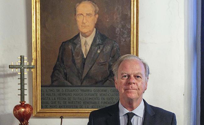 Eduardo Ybarra Mencos posa junto a una pintura de su abuelo, Eduardo Ybarra Osborne, hermano mayor de la Caridad durante más de 20 años / Rául Doblado