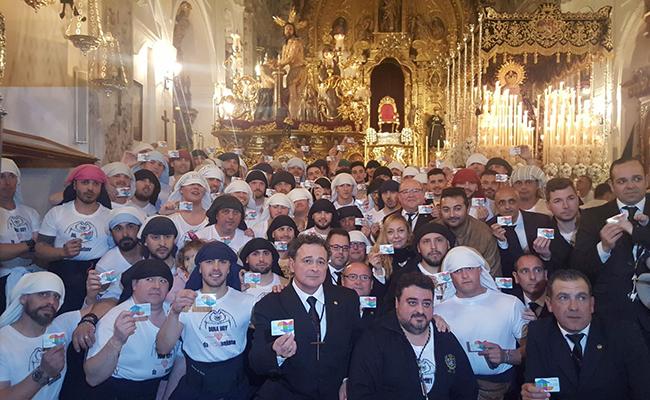 Los integrantes de la hermanda de la Vera-Cruz muestran el carné de donante de órganos