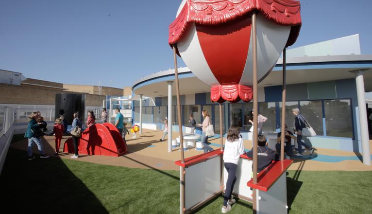 Visita a la azotea azul en el hospital Virgen del Rocío. Dos niños posan bajo lo que simula un globo.