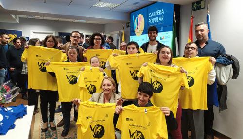 Representantes y usuarios de la Fundación Psicopediatría posan con las camisetas de la carrera