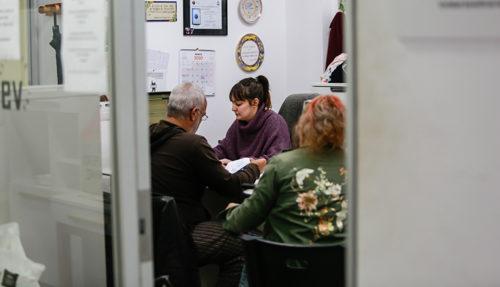 Una trabajadora social atiende a dos usuarios en el despacho