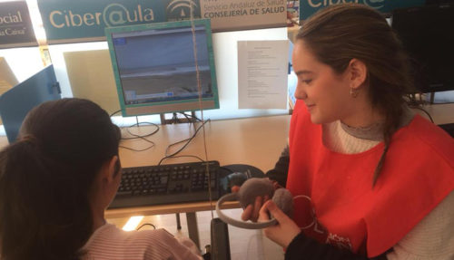 Laura en el Ciberaula del Hospital Infantil Virgen del Rocío sonríe a una niña frente a un ordenador