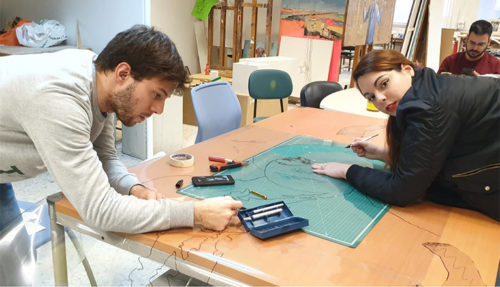 Dos estudiantes trabajan inclinados sobre una mesa con diferentes herramientas de dibujo