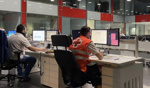 Un voluntario de Cruz Roja ante un ordenador junto a otro empleado también frente a un ordenador