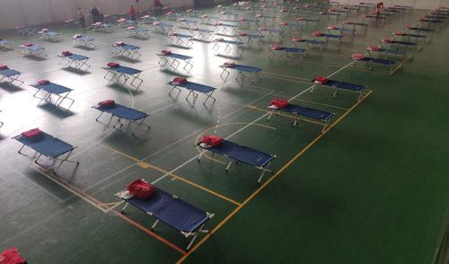 Interior de un pabellón equipado por Cruz Roja para personas sin hogar, con las camas separadas a la distancia recomendada