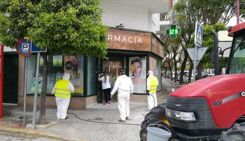 Tres operarios desinfectan una esquina ocupada por una farmacia