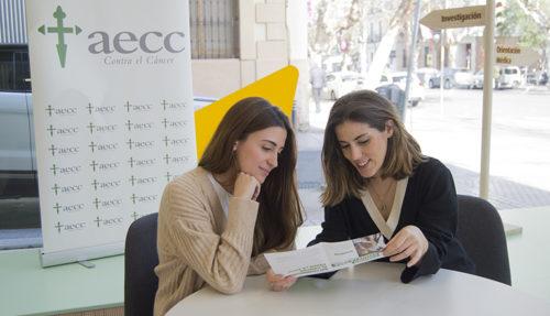 Begoña Sabate, coordinadaro general de voluntariado, está sentada junto a Sherezade frente a una mesa mientras le enseña unos papales. Tras ellas, el logo de AECC.
