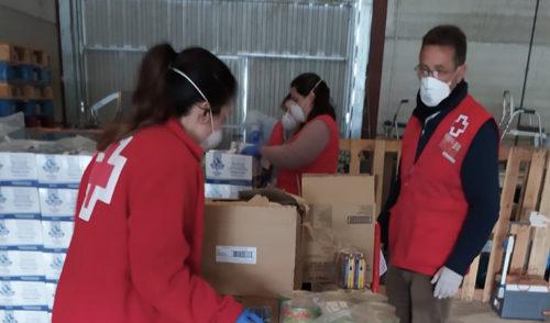 Dos voluntarios de Cruz Roja organizan cajas de alimentos llevando mascarillas y guantes de protección