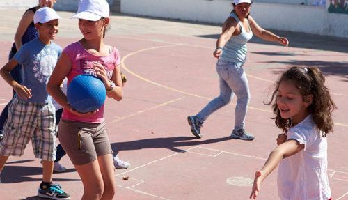 Varios niños juegan al balón en el patio de colegio bajo las instrucciones de una monitora